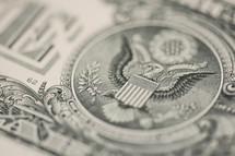 Closeup of a dollar bill showing eagle emblem