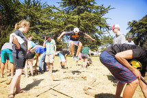 teens building with wood outdoors