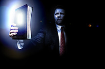 Man in suit holding shining light of the Bible up in the midst of darkness.