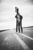 man walking in the center of a highway carrying a large cross - re-enacting Christ's walk, bearing the cross