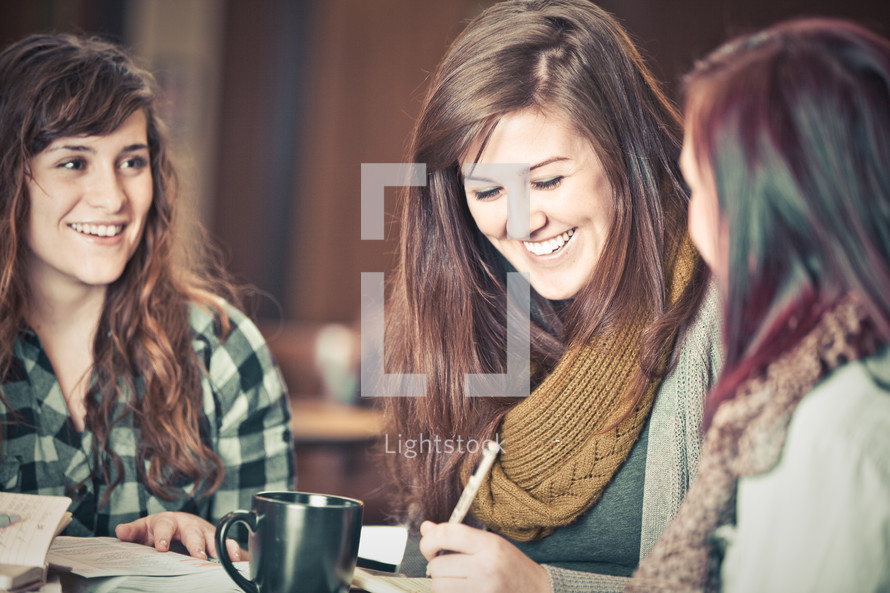 young women smiling as they discuss scripture during a Bible study