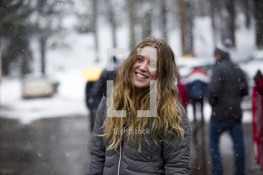 a smiling woman in falling snow