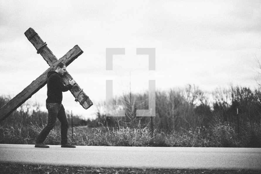 a man walking on a highway carrying a cross  - re-enacting Christ's walk, bearing the cross