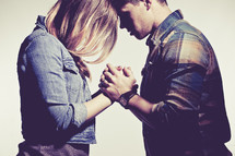 man and woman holding hands together in prayer