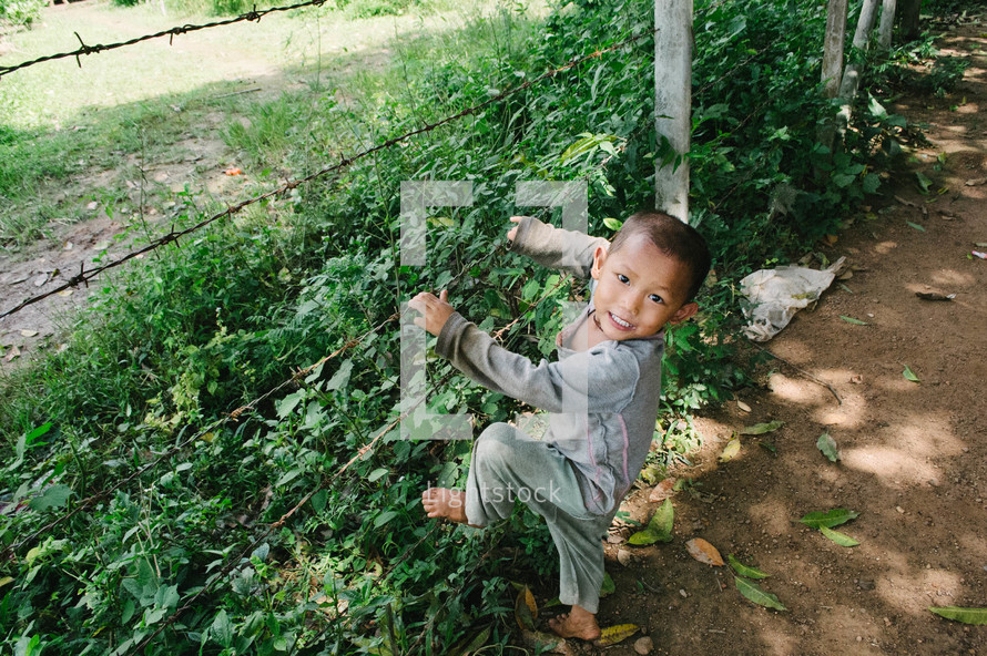 Faces of toddler climbing a barbed wire fence — Photo