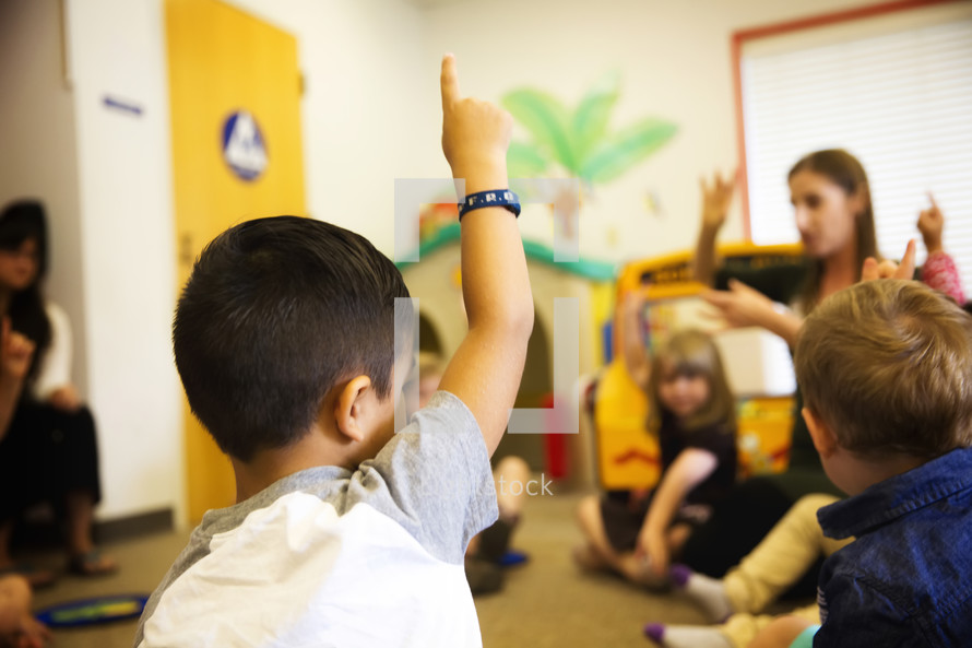 child raising his hand in a classroom