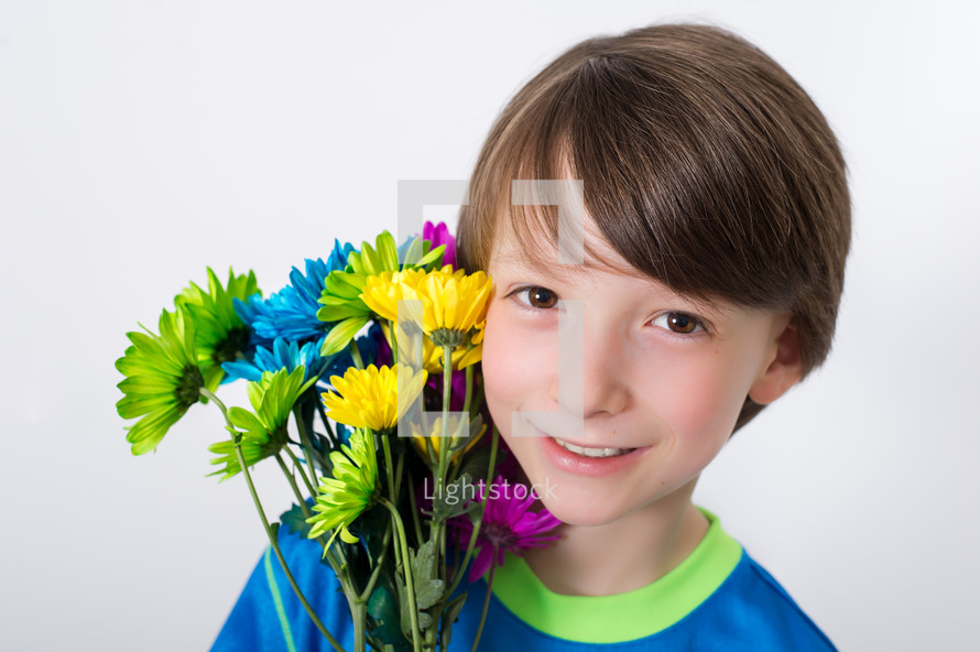 Boy holding a bouquet of flowers by his face.
