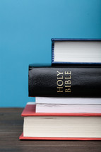 A Bible in a stack of books.