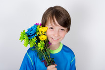 Smiling boy holding a bouquet of flowers by his face.