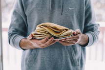 a man holding a plate full of pancakes