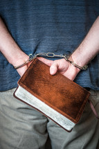 handcuffed man holding a Bible behind his back