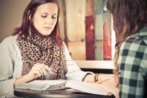 young women reading and discussing the Bible at a Bible study