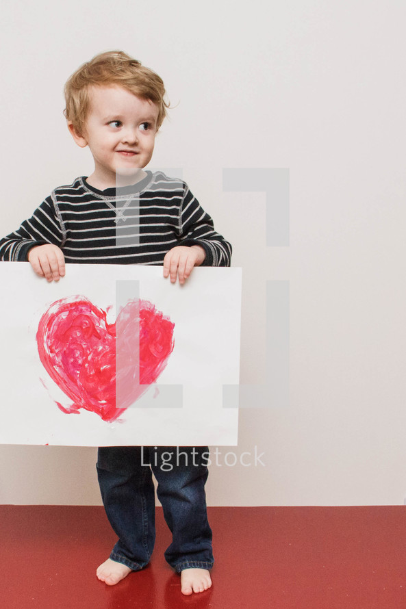 boy child holding a Valentine's picture of a heart