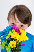 Boy holding a bouquet of flowers in front of his face.