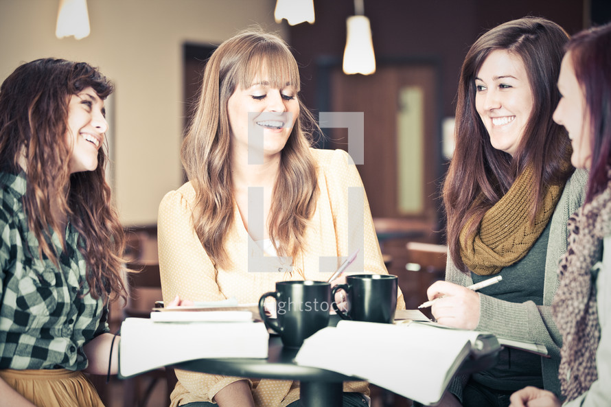 smiling young women discussing scripture at a Bible study