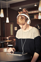 woman in headphones looking at an iPad