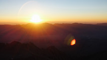 sunrising from behind a mountain