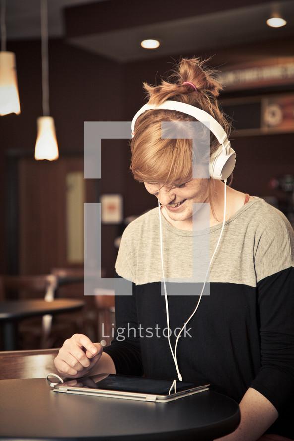 woman wearing headphones looking at an iPad