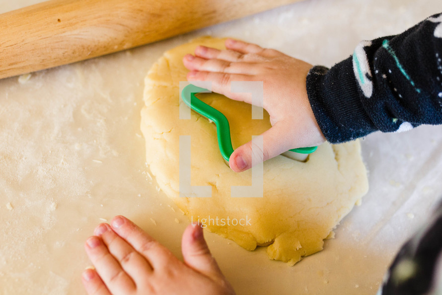 little boy baking christmas sugar cookies