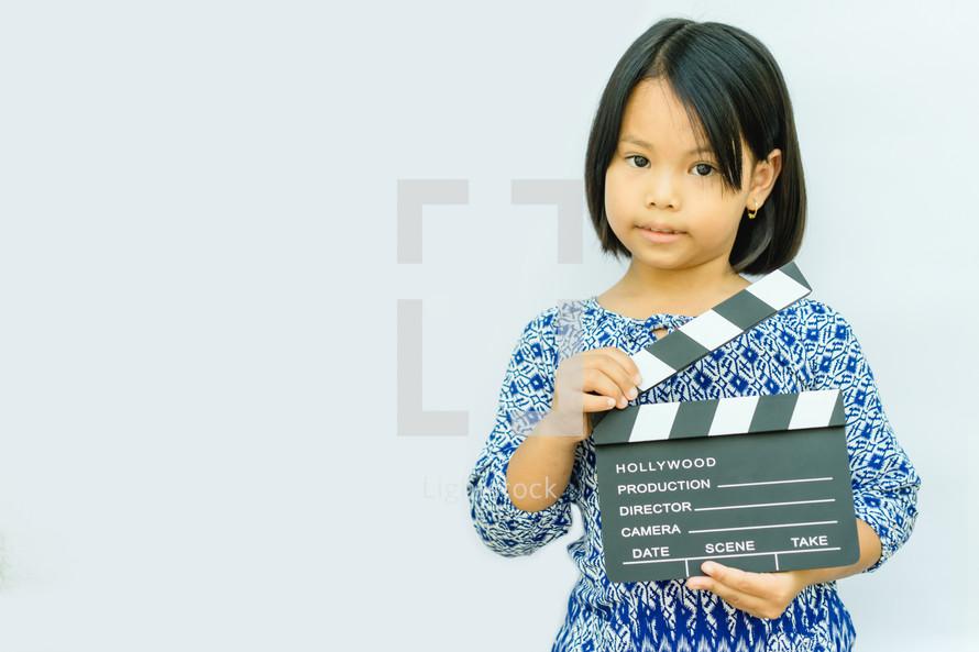 child holding a clapper board