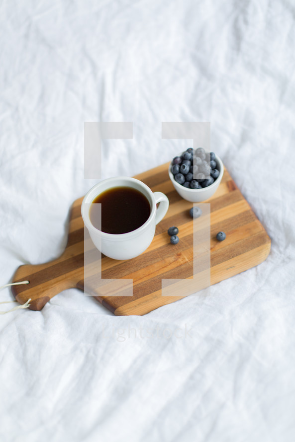 coffee and blueberries on a cutting board
