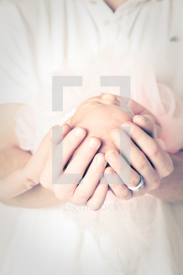 father's hands cradling a newborn infant