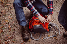 a man fastens his hiking pack
