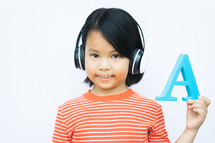 child holding up the letter A with headphones on