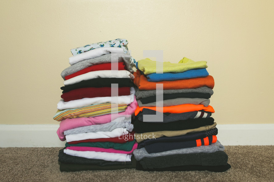 Stacks of folded clothing for boys and girls on the floor