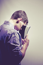 man in prayer to God holding a Bible against his forehead