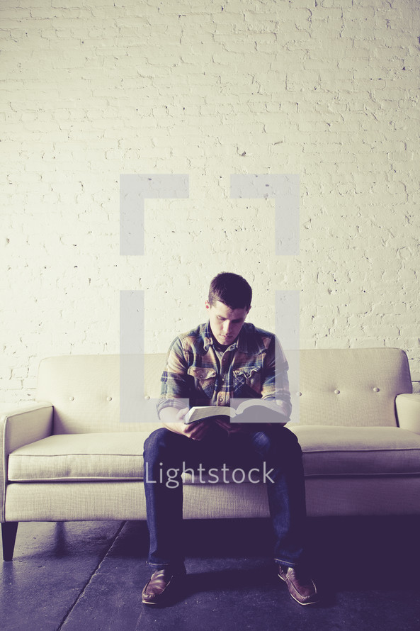 man sitting on a couch reading a Bible