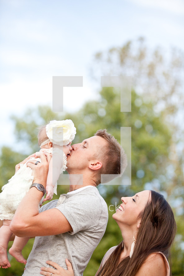 Father kissing infant daughter on the cheek while mother smiles with joy.