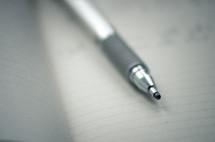 A mechanical pencil on an open notebook