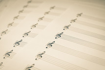 Sheets of empty music manuscript paper with a treble clef on the staff, in black & white (b&w) sepia.