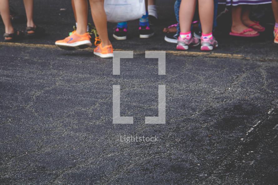 children's feet and shoes on asphalt