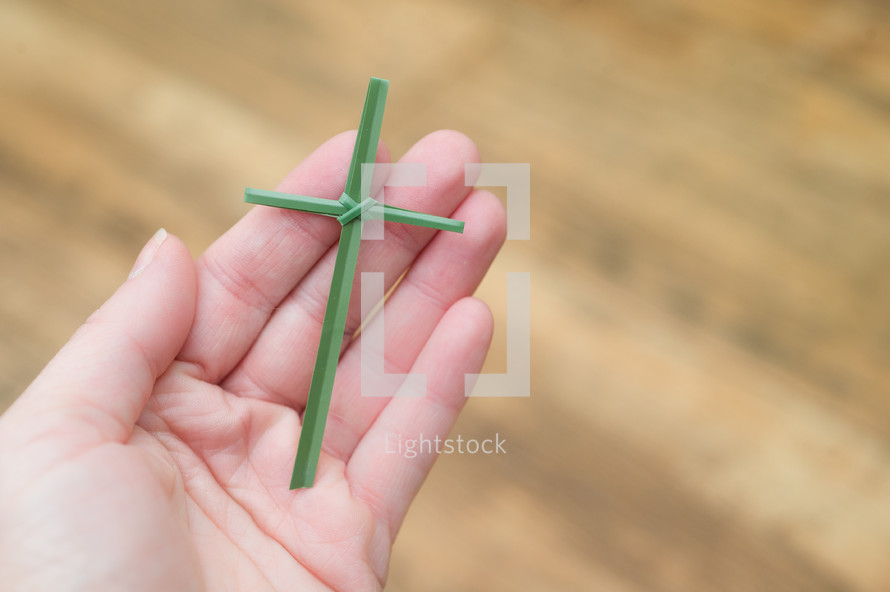 Hand holding flax cross.