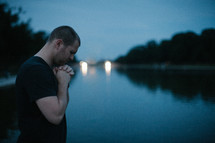 a man in prayer in front of a pond