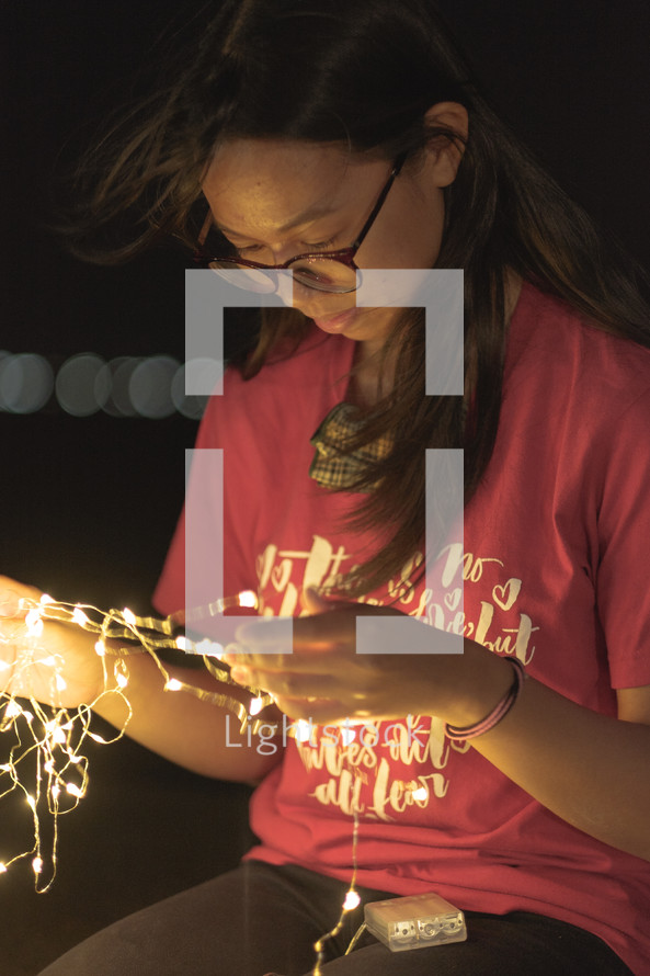 a young woman holding a strand of fairy lights