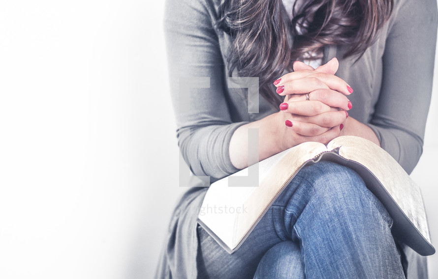 woman praying with a Bible in her lap