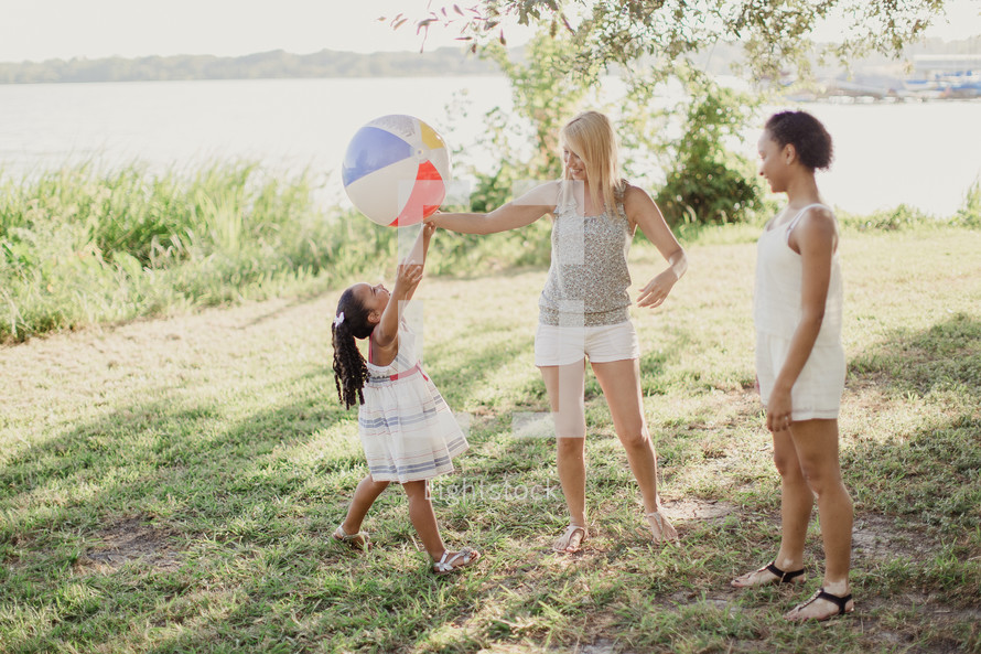 Two young women and a little girl playing with a beach ball.