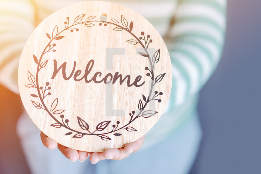 woman holding a welcome sign