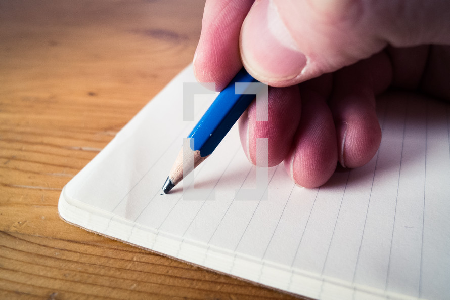A male hand writing with a blue pencil on a blank open notebook