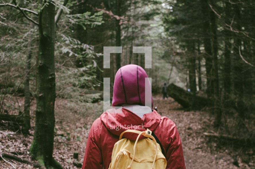 a woman in a pink hoodie hiking on the forest path