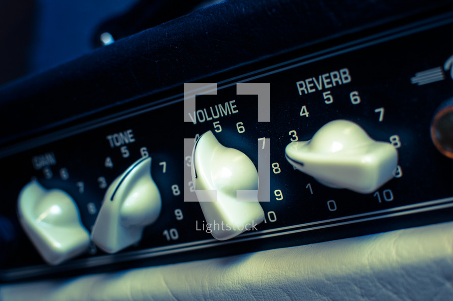 Guitar amplifier level dials: tone, gain, volume & reverb in cross-processed look.