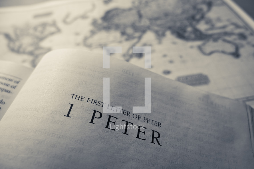 A bible opened to the title page of the first letter of peter (1 peter) with an antique style world map in the background.