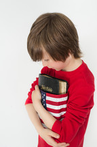 Boy holding a Holy Bible wrapped in an American flag.
