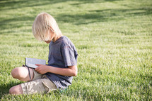 a boy reading a Bible in the grass