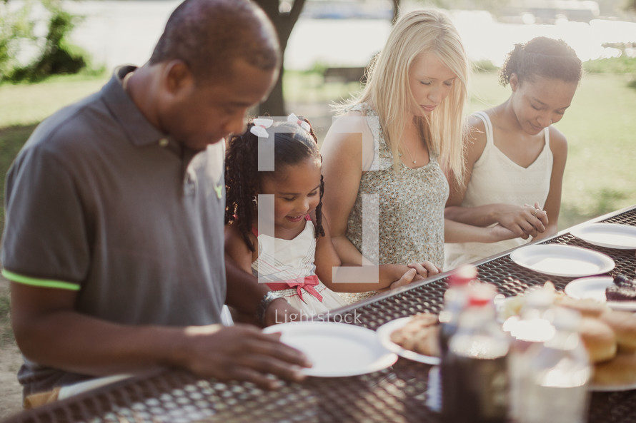 family holding hands in prayer sitting at a picnic table
