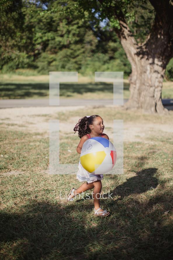 A little girl running outdoors with a beach ball.