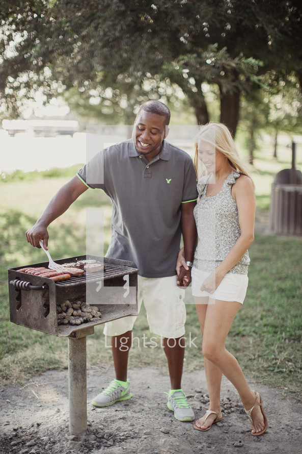 A man and woman holding hands while cooking on an outdoor grill.